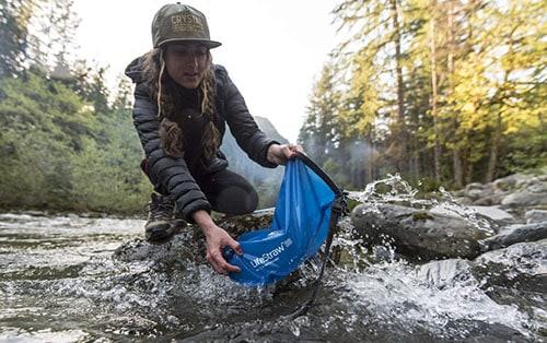 Woman using camping water filter